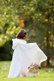 Girl in cape. Little girl in white cape with her shihtzu dog outdoors Royalty Free Stock Images