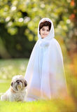 Girl in cape. Little girl in white cape with her shihtzu dog outdoors Stock Photography