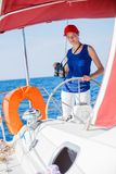 Girl captain on board of sailing yacht on summer cruise. Travel adventure, yachting with child on family vacation. Stock Photography