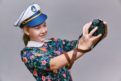 Girl in captain cap makes self camera. stock photos