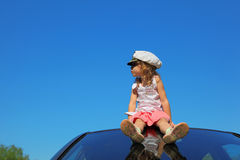 Girl with captain cap sitting on car roof Stock Photos