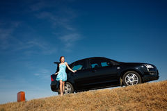 Girl by the car. Puzzled girl with the suitcase near the broken car Royalty Free Stock Photo