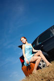 Girl by the car. Puzzled girl with the suitcase near the car Royalty Free Stock Images