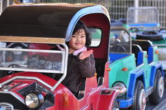 A girl on a car in an amusement park Stock Photos