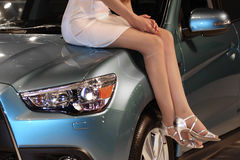 Girl on the car bonnet. The image of girl sits on the car bonnet Royalty Free Stock Photography