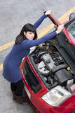 Girl and car breakdown (1). A young girl, holding the car hood open and looking at camera. Shot from a high angle Royalty Free Stock Photos
