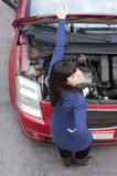 Girl and car breakdown (2). A young girl, holding the car hood open with one hand while looking at camera, above her (shot from a high angle Royalty Free Stock Image