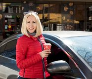 Girl at the car with a  coffee Stock Images