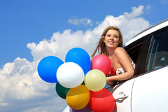 Girl in the car with colorful balloons Royalty Free Stock Photos