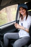 Girl in car holding cell phone Royalty Free Stock Photos
