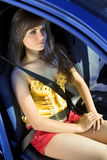 Girl in car fastened by seat belt Stock Photos
