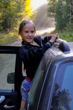 A girl and a car on a forest road in the warm summer morning. The girl is squeamish about car racing. Sunlight falling on the road in the middle of the forest royalty free stock images