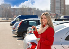 Girl and car. Happy girl with car keys in hand in parking lot royalty free stock photos