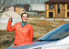 Girl and car. Happy woman with keys in hand over the car at home royalty free stock photo