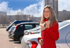 Girl and car. Girl holding the keys to the car hand against parking royalty free stock photos