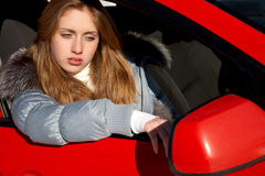 Girl in the car looks a mirror Royalty Free Stock Photography