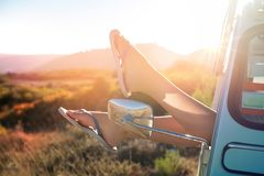 Girl in a car. Girl`s legs in a retro car  at sunset, retro style Royalty Free Stock Image