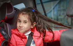 Girl in car seat. Little girl playing with hair in the car seat Royalty Free Stock Photos