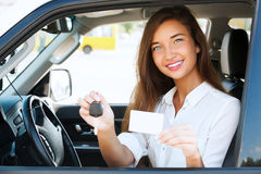 Girl in a car. Showing a key and an empty white card Royalty Free Stock Photos