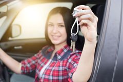 Girl in car showing keys. Close up of pretty young woman in car holding and showing keys in hand Royalty Free Stock Photo