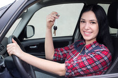 Girl in car showing keys. Pretty young woman in car holding and showing keys in hand Royalty Free Stock Photography