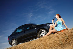 Girl by the car with sunglasses. Puzzled girl with sunglasses near the car Royalty Free Stock Image