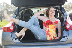 Girl in car trunk with package of flowers Royalty Free Stock Photos