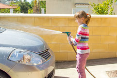 Girl car washing. Cute girl is sprinkling the car from the hose during washing the car Royalty Free Stock Photo