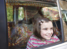 Girl and car window. Girl smiling and looking out of car window at fairground ride with reflection of carousel in glass stock photo
