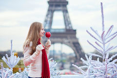 Girl with caramel apple on a Parisian Christmas market Royalty Free Stock Photo