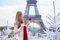 Girl with caramel apple on a Parisian Christmas market. Near white snowy Christmas trees and with the Eiffel tower in the background Stock Photo