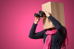 Girl with cardboard box head. Girl holding her cardboard box head with hands on cyan background Royalty Free Stock Photos