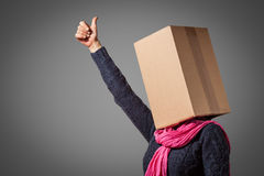 Girl with cardboard box head. Showing her thumb up on gray background Stock Photography