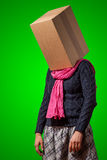 Girl with cardboard box head. Tired girl with cardboard box head on green background Stock Photo