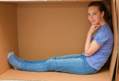 Girl in cardboard box. Teenager girl sits in an empty cardboard box stock photography