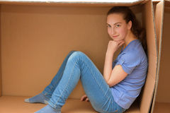 Girl in cardboard box. Teenager girl sits in an empty cardboard box royalty free stock photos