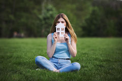 Girl with cardboard figure of house Royalty Free Stock Photos