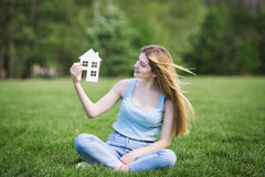 Girl with cardboard figure of house Royalty Free Stock Photography