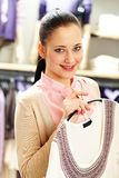 Girl with cardigan. Portrait of pretty woman holding cardigan and looking at camera in clothing department Royalty Free Stock Image