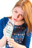 Girl carefully considering money through magnifier Stock Photography