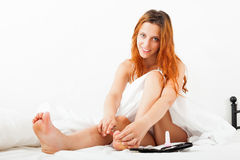 Girl cares for toenails with scissors in bed Stock Photography