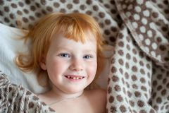 A girl with caries smiles. On the bed Royalty Free Stock Images