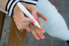 Girl caring for cuticles while sitting on a bench in the street. A young girl with bright pink manicure gets oil on the cuticles sitting on a bench on the street Royalty Free Stock Images