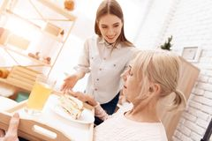 Girl is caring for elderly woman at home. Girl brings breakfast on tray. Woman is eating sandwitch. Girl is caring for elderly women in wheelchair at home. Girl Stock Photos