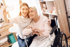 Girl is caring for elderly woman at home. They are taking selfie on phone. stock photography