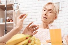 Girl is caring for elderly woman at home. Girl brings breakfast on tray. Woman is refusing to eat fruit. stock photography