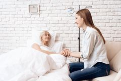 Girl is caring for elderly woman at home. They are holding hands. royalty free stock photos