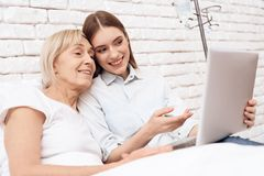 Girl is caring for elderly woman at home. They are using laptop. They are happy. stock photos