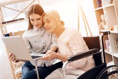 Girl is caring for elderly woman at home. They are using laptop. Girl is caring for elderly women in wheelchair at home. They are using laptop stock photography