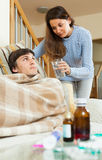 Girl caring for sick husband in living room Royalty Free Stock Image